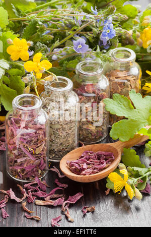 healing herbs in glass bottles, healthy flowers and wooden spoon, herbal medicine Stock Photo