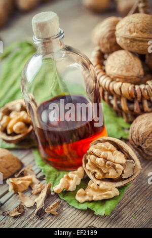 Walnuts, bottle of tincture or oil and wicker basket with nuts on old kitchen table. - Stock Photo