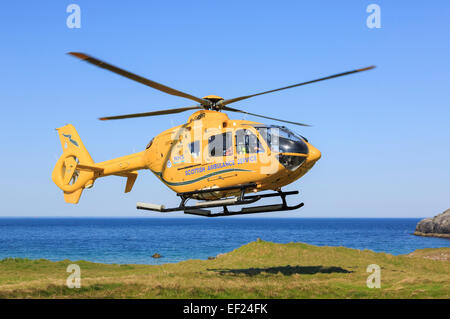 Scottish Air Ambulance Service Helicopter taking off after a rescue mission on remote North West Highlands coast. - Stock Photo