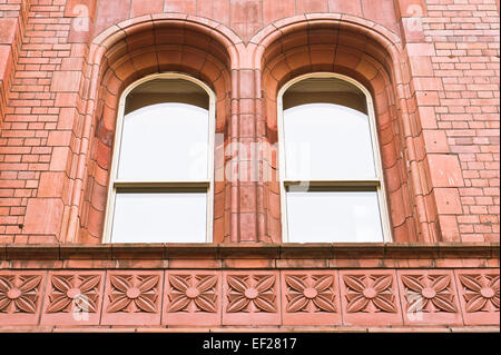 A pair of arch windows in a red brick building in Manchester, UK - Stock Photo