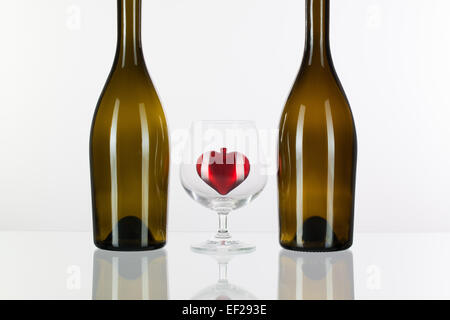 Two bottles and red heart inside a glass of cognac on a glass plate - Stock Photo