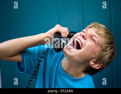 Child 10,11,12,13 laughing while talking on telephone, holding receiver - Stock Photo