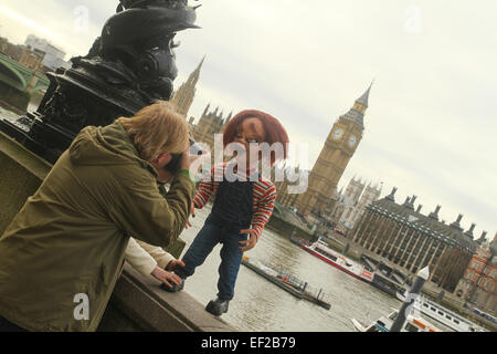 London, UK. 25th January, 2015. A man takes a photos of a Chuky looking doll on the south bank of the river Thames. - Stock Photo