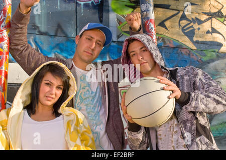 Three teenagers posed in front of a graffiti covered wall - Stock Photo