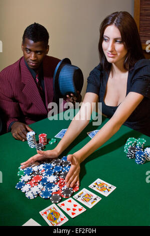 Woman picking up chips in a poker game - Stock Photo