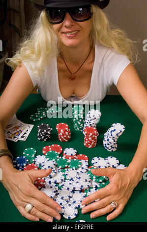 Woman picking up chips in a game of poker - Stock Photo