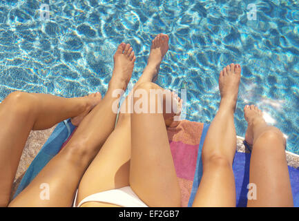 The legs of three girls on a poolside - Stock Photo