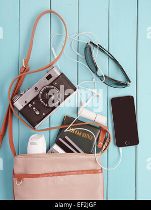 female bag with a variety of personal belongings and with retro camera. set traveler - Stock Photo
