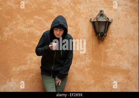 Dark young woman sad standing and smoking near urban wall portrait - Stock Photo