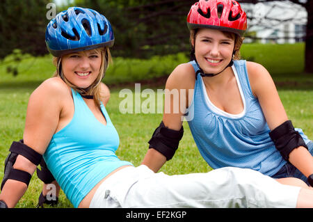 Two women at a park wearing inline skates - Stock Photo