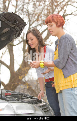 Two women looking under hood of car - Stock Photo