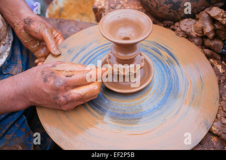 artisan potter molding a piece of clay on a lathe - Stock Photo