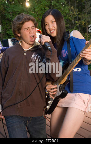 Teenage band playing on an outdoor deck - Stock Photo