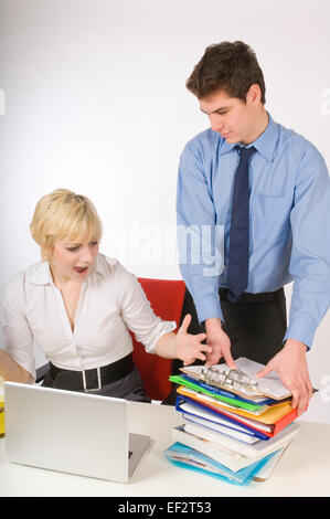 Businessman bringing paperwork to female colleague - Stock Photo
