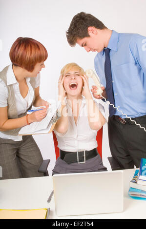 Overworked woman at her desk - Stock Photo