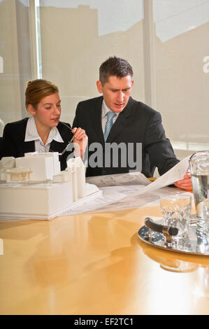 Architects looking at blueprints - Stock Photo