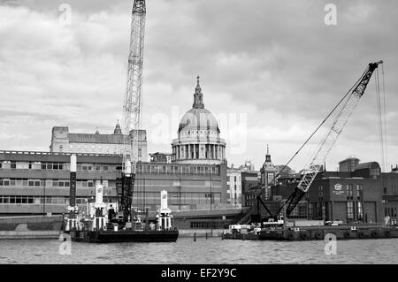 Black and white view of St Paul's Cathedral framed by two floating cranes, seen from the River Thames, London, England - Stock Photo