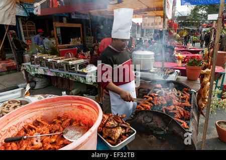 Street kitchen at the Pokhara Street Festival, Nepalese woman barbecuing meat, Pokhara, Nepal - Stock Photo