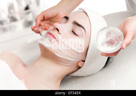 Young woman peeling foam mask applying on face - Stock Photo