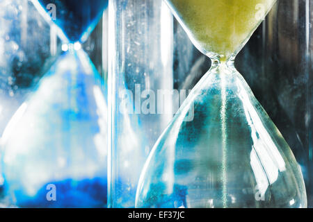 timer hourglass streaming grains of sand flowing through depicting things are running out - Stock Photo