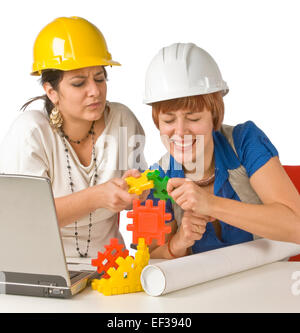 Two women playing with child's building toy - Stock Photo