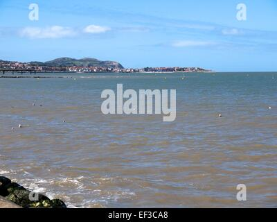 Rhos on Sea in the distance and the sea in the foreground - Stock Photo