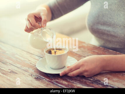 close up of female pouring milk into coffee - Stock Photo