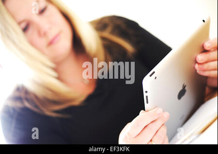 Blonde hair white woman sitting at desk using apple ipad for business work, bright light shining through - Stock Photo