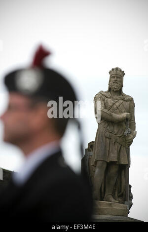 A man dressed in traditional Scottish outfit is framed by the state of Robert the Bruce before the start of Pipefest, - Stock Photo