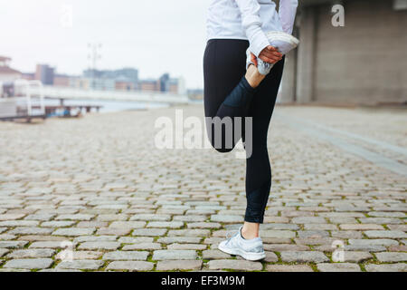 Low section view of fit young woman stretching her leg before a run in city streets. Preparation for running workout. - Stock Photo
