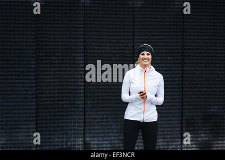 Portrait of happy young woman listening to music on mobile phone. Female runner relaxing after a training session. - Stock Photo