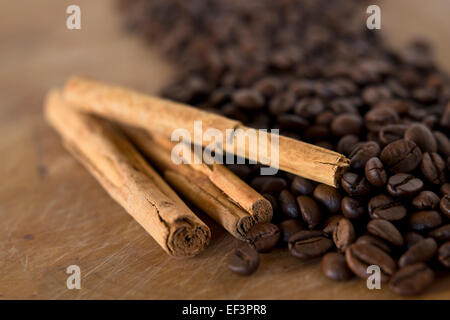 Detail of a pile of coffee beans and cinnamon sticks background - Stock Photo