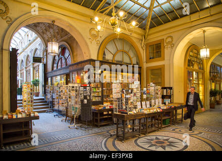 Man walks past corner bookstore in Passage Vivienne - one of the covered passages of the 2nd Arrondissement, Paris - Stock Photo
