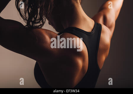 Close-up shot of back of female fitness model. Young woman in sports wear with muscular body. - Stock Photo