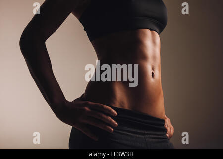 Mid section of strong young woman torso with her hands on hips. Abs of female  athlete in sportswear. - Stock Photo