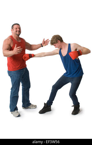 Man wearing boxing gloves punching another man - Stock Photo
