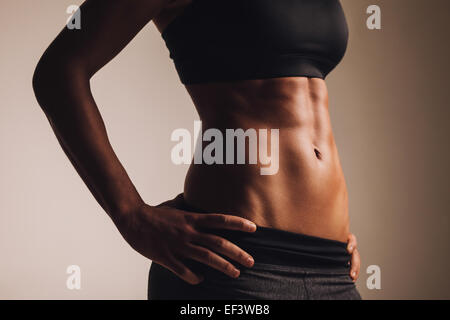 Close-up shot of young woman waist with muscular abdominal muscles. Abs of fit female athlete. - Stock Photo