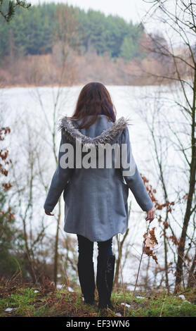 Young girl with her hair stands near the water - Stock Photo