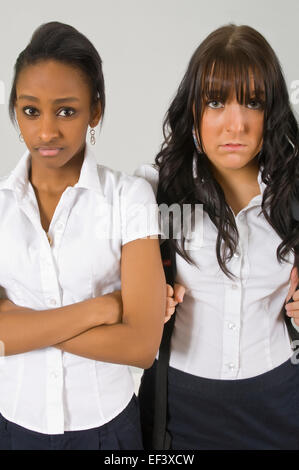 Two unhappy young women standing side by side - Stock Photo