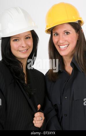 Two women wearing hard hats - Stock Photo