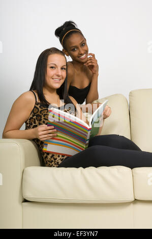 Two women looking at book together - Stock Photo