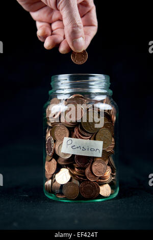 Adding a penny to a pension pot. - Stock Photo