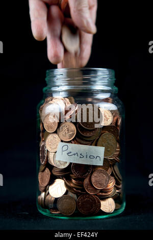 Adding some pennies to a pension pot. - Stock Photo