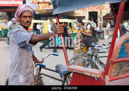 Agra, India, South Asia. Bicycle rickshaw driver waiting for customers at Kinari bazaar - Stock Photo