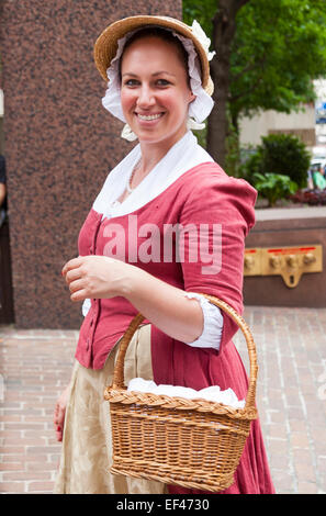 Woman dressed in traditional colonial costume, holding a wicker basket, Freedom Trail, Boston, Massachusetts, USA - Stock Photo