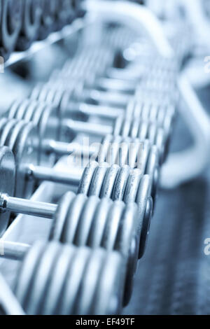 Dumbbells in gym. Soft blue tint. - Stock Photo