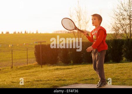 boy playing tennis in backyard - Stock Photo