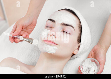 Young woman facial peeling mask applying in beauty parlour - Stock Photo