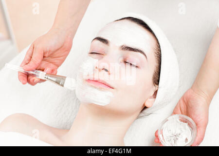 Young woman facial mask applying in beauty parlour - Stock Photo