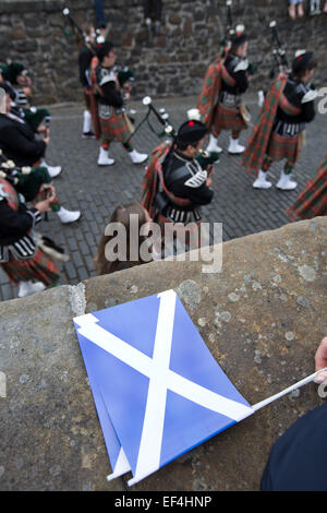 A Scottish saltire lying on a wall as a traditional Scottish pipe band marches past during Pipefest Stirling, an - Stock Photo
